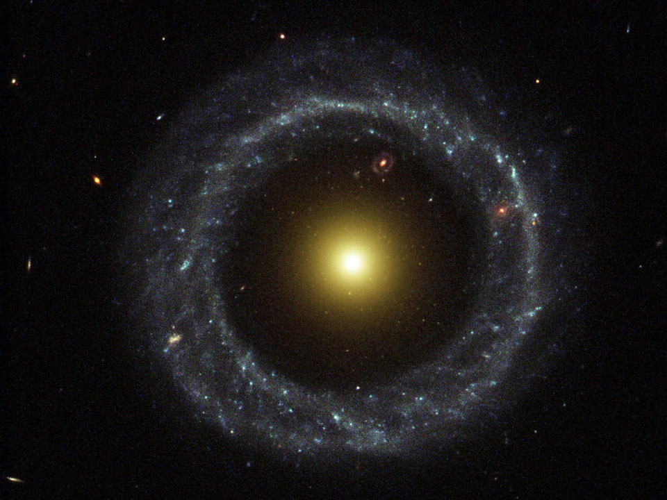 On the outside is a ring dominated by bright blue stars, while near the center lies a ball of much redder stars that are likely much older. Between the two is a gap that appears almost completely dark... Coincidentally, visible in the gap (at about one o'clock) is yet another ring galaxy that likely lies far in the distance.